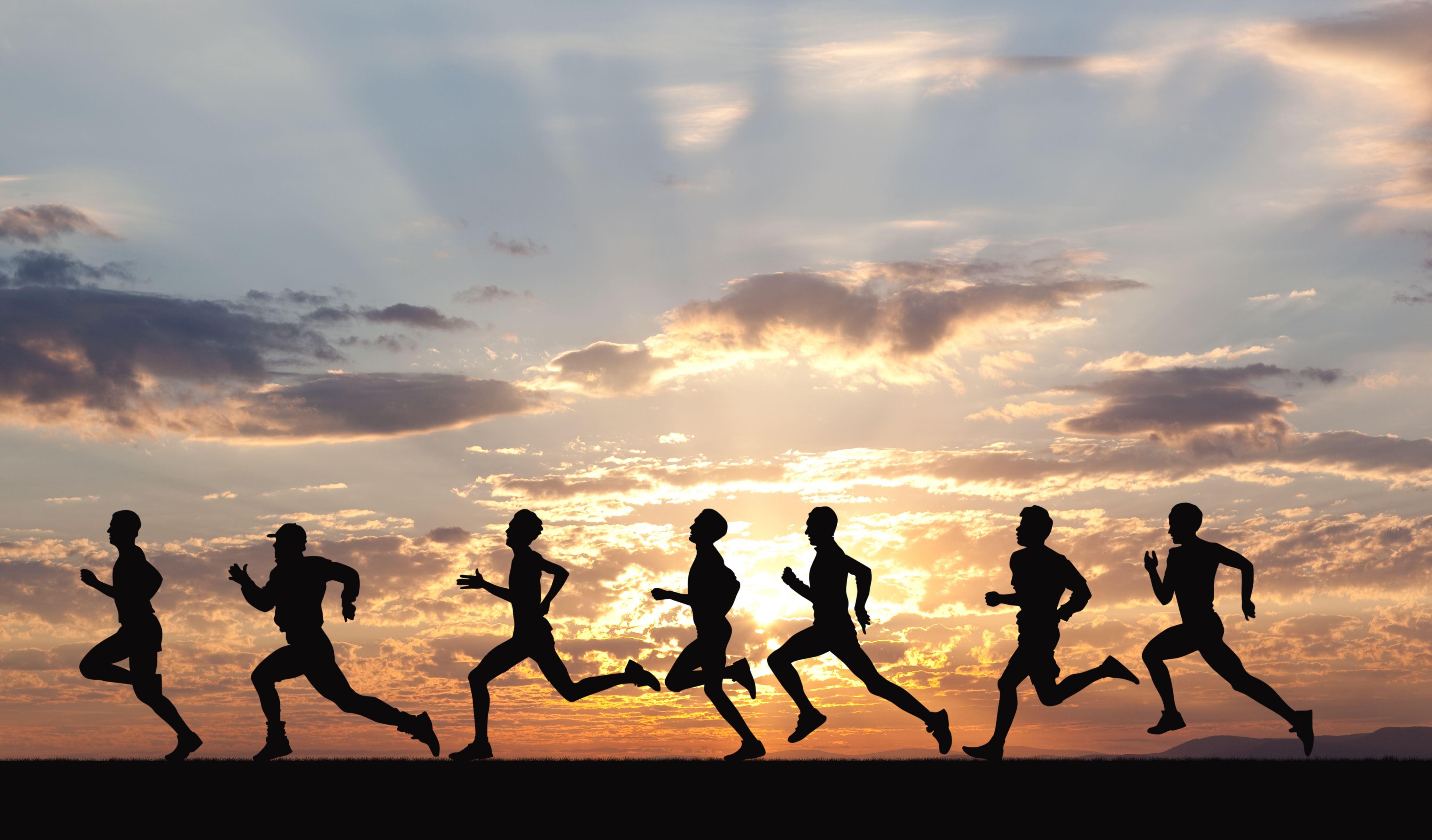 Marathon, black silhouettes of runners on the sunset